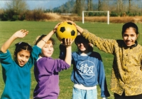 Four girls on a soccer field touching yellow soccerball