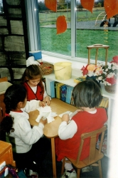 Three girls sitting at table by window working with paper. Orange leaf decals on window. C. Nov 1996