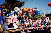 People siting on parade float wtih balloons and cow statue (Pitt Meadows Day 2004?). Balloons on far right have