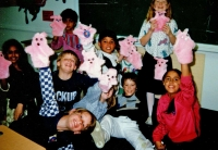 Children holding furry, pink puppets in the air C.1986/87