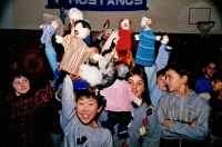 Children with puppets on hands, holding them in the air C.1987