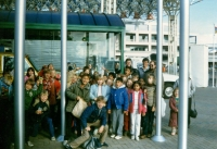 Group of children and supervisors smiling for camera outside around flagpoles C. 1986/87