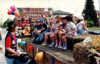 Meadowland Country Fair float in parade. Children sitting on hay barrels atop float, being addressed by woman on left on sidewalk. C.1990