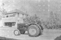 Hans on tractor in front of General Store, with upper porch. 1950s