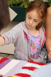 A child painting her tic-tac-toe board