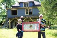 Curator L. Norman, Bjorn, and Bill Veltin holding up a stained glass window from the house.